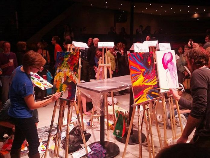 """Paul putting some polish to his Round 1 masterpiece at Art Battle sporting his red """"victory cap""""."""