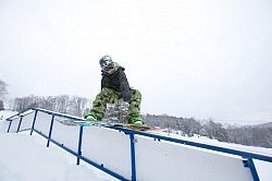 A snowboarder rides a rail at Sir Sam's terrain park