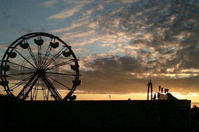 The sun going down on the Lindsay Fair; a few folks still seem to be in the ferris wheel, perhaps enjoying the view (photo: Carol Lawless)
