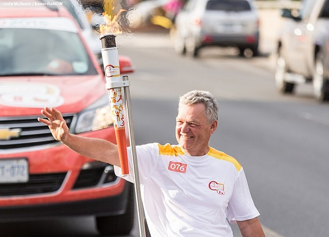 Warsaw Paralympian archer Alec Denys was the final torchbearer and carried the flame into Del Crary Park to light the community cauldron (Photo: Linda McIlwain / kawarthaNOW)