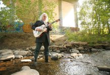 """Local songwriter and musician Dennis O'Toole participating in """"Going Down to Jackson"""", a project by Esther Vincent featuring photos of people from all over Peterborough wearing rubber boots and standing in Jackson Creek. The photos will be presented as an outdoor slideshow projection in downtown Peterborough during Artsweek from September 18 to 27. (Photo: Esther Vincent, www.evmustang.ca)"""