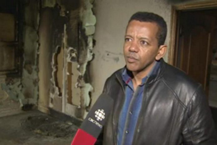 Kenzu Abdella, president of the Kawartha Muslim Religious Association, being interviewed by CBC Television as he surveys the fire and smoke damage to the mosque (photo: CBC Television)