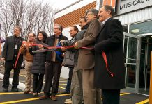 Cutting the ribbon at the official opening of Peterborough's new Long & McQuade store (from left to right): CEO & President Steve Long, councillor Keith Riel, MP Maryam Monsef, MPP Jeaf Leal, Bud Monahan, unidentified, Warden J. Murray Jones, councillor Dave Haacke
