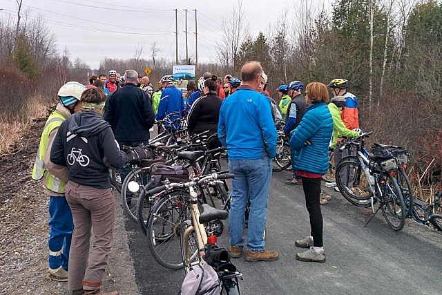 A crowd of cyclists and others gather for the official trail opening on November 10