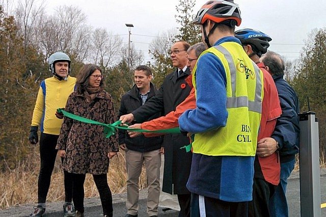 The official ribbon cutting with cyclists Rick and Dave, Susan Sauve, Michael Goodyear, Daryl Bennett, Keith Riel, and more