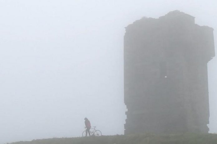 """Megan Murphy with her father's bicycle at the Cliffs of Moher in County Clare in a scene from """"Murphy's Law"""", the documentary of her journey across Ireland"""