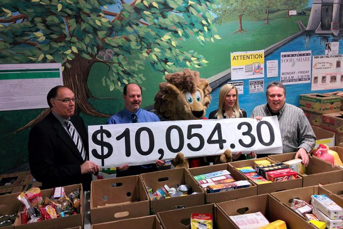 Ashlee Aitken of Kawartha Food Share (second from right) accepts the $10,054.30 donation from (left to right) Peterborough Mayor Daryl Bennett, the City of Peterborough's Manager of Transportation Kevin Jones, DBIA mascot George King of Downtown, and DBIA Executive Director Terry Guiel (photo courtesy Peterborough DBIA)