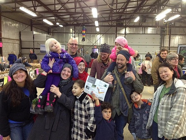 Lise Fines (left), a member of the Salaam Peterborough sponsor group, with the Alkhalaf family and members of three other families in the sponsor group at the Peterborough Farmers' Market in January (photo: Rick Fines, courtesy of Lise Fines)