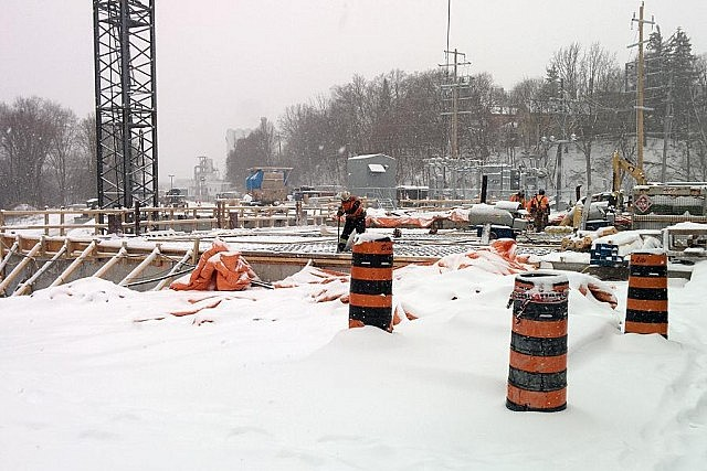 Construction workers at the foundation of the new power plant. The generators in the background covered by tarps will be lowered into the location below the workers.