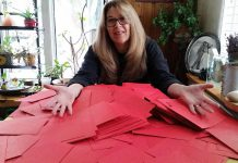 Author Mary Giuffre, who rescued Ruby from a puppy mill, with red envelopes representing letters she hopes people send during the Valentine's Day letter campaign to shut down puppy mills