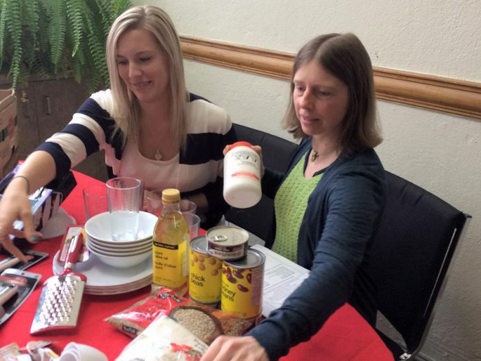 Kawartha Food Share's Ashlee Aitken and NCC's Tamara Hoogerdyk with examples of the food and kitchen-related items they are asking the public to donate to help welcome Syrian refugee families settling in Peterborough (photo courtesy of New Canadians Centre)