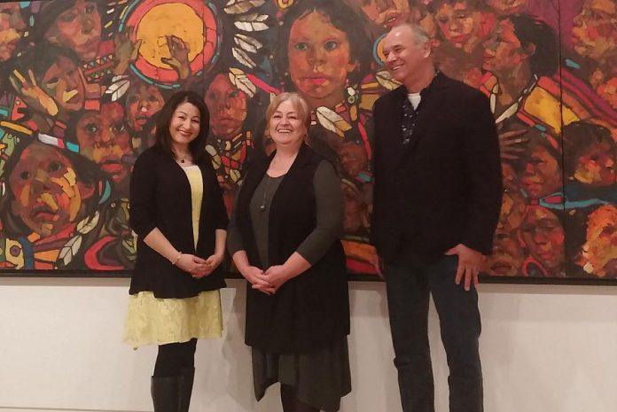 """Peterborough-Kawartha MP Maryam Monsef, Art Gallery of Peterborough director Celeste Scopelites, and curator William Kingfisher in front of """"The Beauty of Our People"""" by local artist Arthur Shilling (photo: Art Gallery of Peterborough)"""