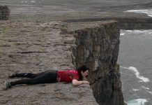 Megan Murphy lying at the edge of a cliff on the Aran Island in Ireland in a scene from her documentary film Murphy's Law, which chronicles her journey to retrace her deceased father's bicycle trip across Ireland (photo courtesy of Megan Murphy)
