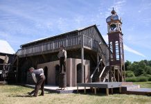Part of the set for 4th Line Theatre's original production The Hero of Hunter Street at the Winslow Farm in Millbrook, with a reproduction of the downtown Peterborough clock tower in the background (photo: Jeannine Taylor / kawarthaNOW)
