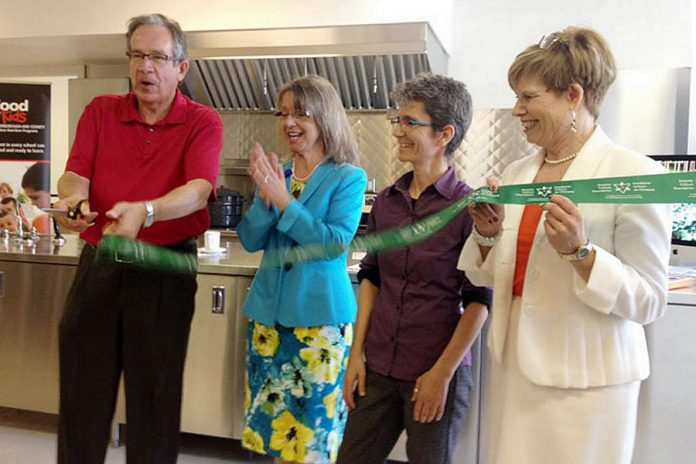MPP Jeff Leal cuts the ribbon at Myrtle's Kitchen at the downtown location of the newly rebranded Peterborough Public Health, as Medical Officer of Health Dr. Rosana Salvaterra, Jillian Bishop of The Nourish Project, and Leslie Orpana of the Ontario Trillum Foundation look on (photo: Paul Rellinger / kawarthaNOW)