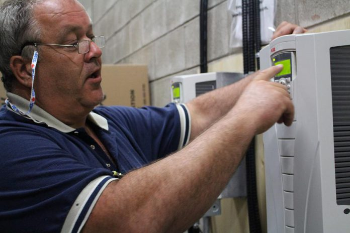 Jansen demonstrates how the Variable Frequency Drives (VFDs) enable Peterborough Square to save on energy use by matching the energy of large motors to what is needed, eliminating energy waste by not using more than is necessary.