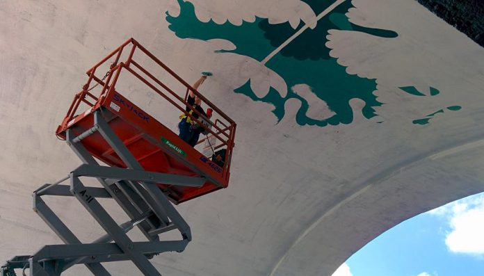 Edmonton artist Jill Stanton on the scissor lift under the Hunter St. Bridge in Peterborough. After completing a pencil outline, she has begun to paint her bloodroot mural design. (Photo: Bruce Head / kawarthaNOW)