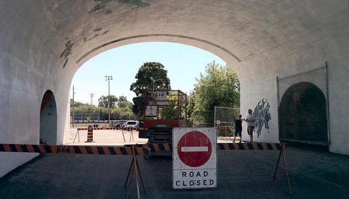 Jill consults with her assistant as they begin the painting process. The road under the archway is closed while the work is underway. (Photo: Bruce Head / kawarthaNOW)