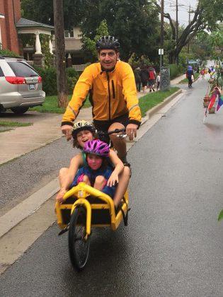 John Hauser, owner of a Bullitt cargo bike, takes two children for a ride at the King Street Pulse Pop-Up on September 17. The cargo bike can be adapted with tubs, lockable boxes, canopies, flat boards, or child seats, depending on personal needs.