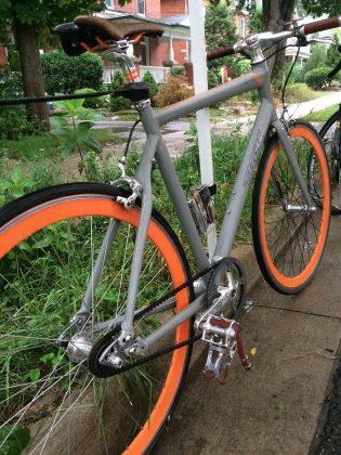 A single-speed bike with orange rims and a belt drive in place of a chain; a simple, clean design that requires less maintenance while the sleek lines make it easy to modify and customize, and without all the added gears, this is a cheaper to purchase.