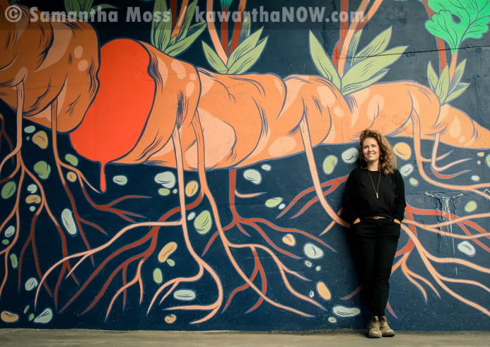 Artist Jill Stanton stands in front of a portion of her mural (photo: Samantha Moss / kawarthaNOW.com)