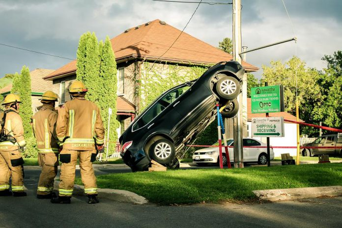 Firefighters look at the scene of an accident in East City, Peterborough, where a car climbed up a hydro pole. The car is being held in place with various supports until it can be safely lowered to the ground. (Photo: Samantha Moss)