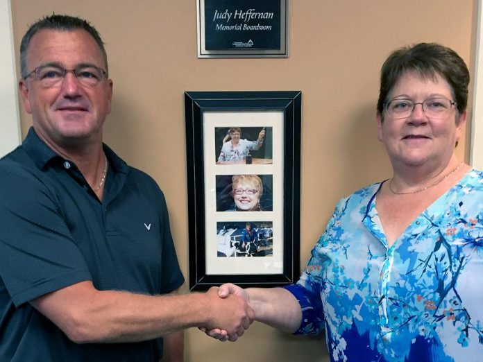 Kim Appleton, chair of the Community Futures Peterborough Board of Directors, welcomes Jeff Day as the organization's new Executive Director. In the background is the memorial boardroom for Judy Heffernan, who served at General Manager for 17 years before passing away suddenly in 2013.