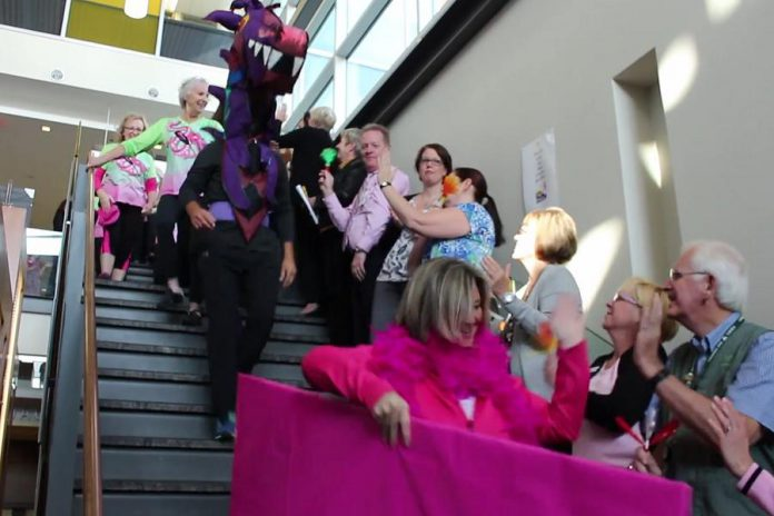 Staff at Peterborough Regional Health Centre cheer on Peterborough's Dragon Boat Festival organizers and volunteers (and the dragon mascot, inhabitated by Billy Thornton) as they arrive at the hospital with the cheque  (photo: Impact Communications / PRHC Foundation)