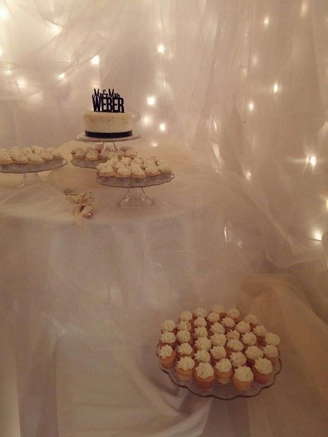 Gone are the barn board and beer signs. Swanky Events created a more elegant backdrop for the wedding cake with soft white tulle and twinkle lights. (Photo: Sue Swankie)