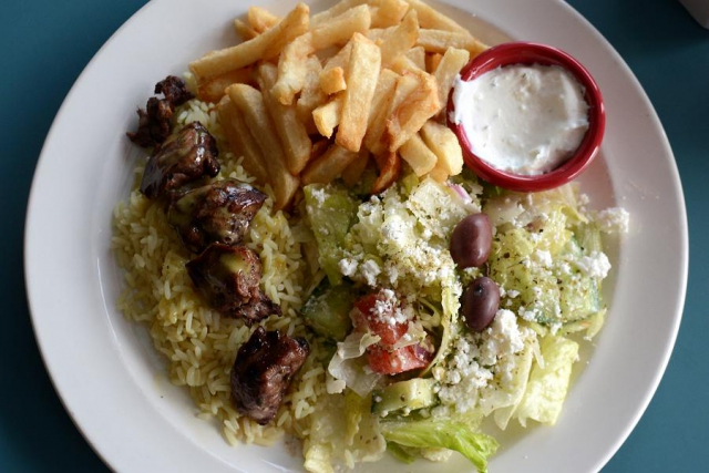 Souvlaki is a popular menu item. It is served with Greek salad and fries made from local potatoes. (Photo: Eva Fisher)