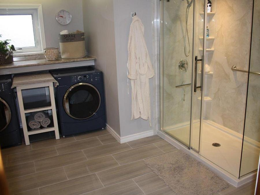 Tight on space? A glass walled shower makes the room feel more spacious and a washer and dryer nook makes the most of every square foot. (Photo: Peterborough Bath Renovators)
