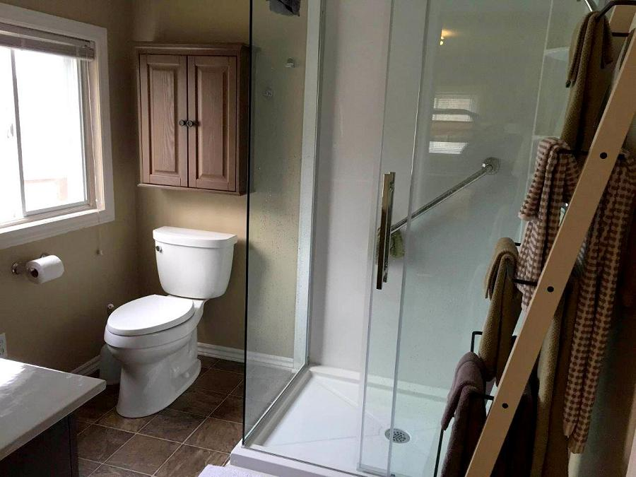 The team works hard to make accessibility features like grab bars in this elegant glass walled shower look good with the room's design. (Photo: Peterborough Bath Renovators)