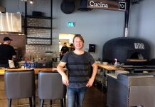 Co-owner and Manager Matt Choma stands in front of the wood-fired pizza oven in the restaurant section of One Fine Food, a new Italian-inspired restaurant and marketplace opening this week in Peterborough. (Photo: Eva Fisher / kawarthaNOW)