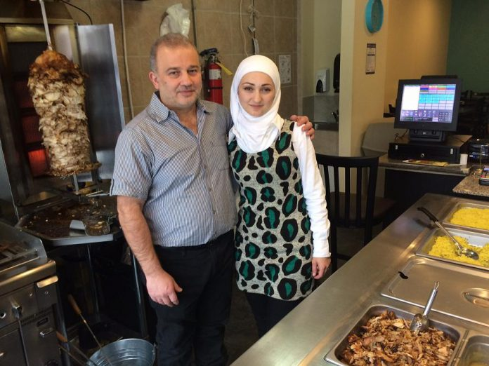 Syrian refugees Mohammad and Randa Alftih pose with some of the authentic Mediterranean food served at their new restaurant, OMG, in downtown Peterborough. (Photo: Eva Fisher / kawarthaNOW)