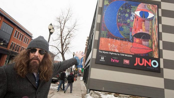 """When he stopped drinking in 1997, Tom Wilson began painting in his unique Picasso-like style, which includes intricate inscribing of song lyrics and stories onto the canvas. Here he's pictured in front of """"The Mystic Highway"""", a mural commissioned by the Canadian Academy of Recording Arts and Sciences and the City of Hamilton for the 2015 Juno Awards. (Photo: The Canadian Press / Peter Power)"""