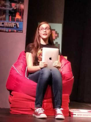 "Aimee Gordon as Gamer Girl during a dress rehearsal for ""The Reluctant Dragon"". Her character plays the video game in which the play's action takes place and she addresses the audience.  (Photo: Sam Tweedle / kawarthaNOW)"