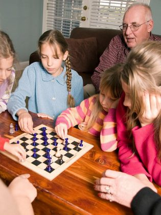 Family literacy isn't just about reading together. It's also about engaging together in other family learning activities such as playing board games.
