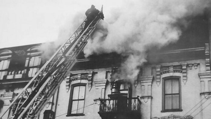 A firefighter battles a fire on the third floor of The Pig's Ear in 1949. The building originally had four storeys, but the fourth storey was seriously damaged by a fire in the 1930s and was never rebuilt.