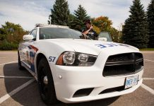 A Peterborough police officer standing beside a police cruiser. (Photo: Peterborough Police Service)