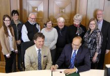 Peterborough Symphony Orchestra Music Director and Conductor Michael Newnham sits beside Mayor Daryl Bennett as he signs the proclamation of Symphony Week in Peterborough, with staff and supporters of the Peterborough Symphony Orchestra in the background (photo: Bruce Head / kawarthaNOW)