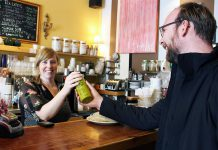 Maggie Lightfoot passes a bottle of tap water over the counter to GreenUP Water Programs Coordinator Dylan Radcliffe at Black Honey Coffee House on Hunter Street, Peterborough. Black Honey is one of many businesses that have signed up as part of BlueWPtbo.ca, an online app mapping businesses in the city where anyone can fill up their reusable water bottle for free. (Photo courtesy of GreenUP)