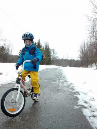 Beck Akiyama wears a warm coat, waterproof pants, winter gloves, and a balaclava to stay warm and dry while biking along the Rotary Trail in East City, Peterborough (photo courtesy of GreenUP)