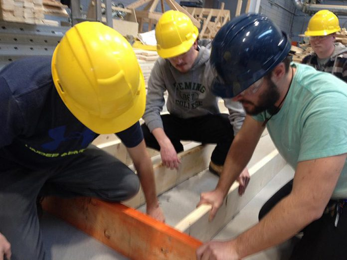 Fleming College Carpentry Techniques students Daniel Widdis, Carter Clark, and Benjamin Wright working on a wall frame destined for the new Peterborough County Agricultural Heritage Building at Lang Pioneer Village in Keene (photo: Paul Rellinger / kawarthaNOW)