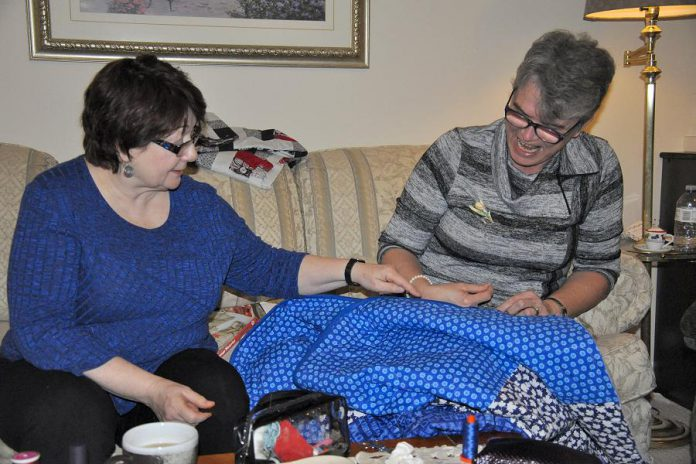 Colleen Carruthers, who is coordinating the 150 Canadian Women Quilt project for the Peterborough Women's Business Network, with fellow quilter Debbie Fisico. (Photo: Jeanne Pengelly / kawarthaNOW)