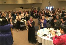 With tears and smiles, the 150 women attending Peterborough's first International Women's Day Conference give a standing ovation to feminist comic and actor Candy Palmater (left) following her morning keynote (photo: Jeanne Pengelly / kawarthaNOW)