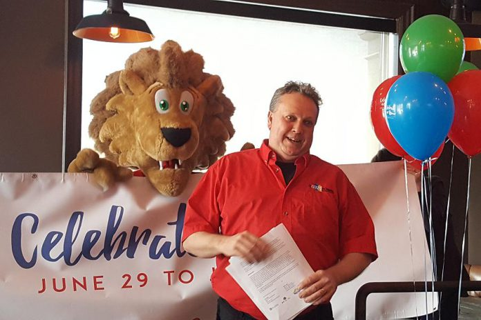 Terry Gueil, Executive Director of Peterborough DBIA, announces the line-up of Canada 150 festivities in downtown Peterborough, with mascot King George in the background (photo: Jeannine Taylor / kawarthaNOW)