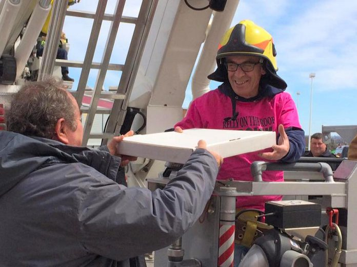 "Using its aerial ladder, the Peterborough Fire Department will deposit Paul ""Relly"" Rellinger on the roof of The Brick. Here he is at last year's event, accepting a pizza donated by Peter Bouzinelos of The Pizza Factory. (Photo: Habitat for Humanity)"