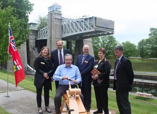 At the event announcing $9 million in provincial funding for the new canoe museum, Peterborough MPP Jeff Leal is invited to carve a canoe paddle, symbolic of the journey to the new facility to be built beside the Peterborough Lift Lock. Also pictured are representatives from The Canadian Canoe Museum, Peterborough Mayor Daryl Bennett, Curve Lake First Nation Chief Phyllis Williams, and Peterborough County Warden Joe Taylor. (Photo: The Canadian Canoe Museum)