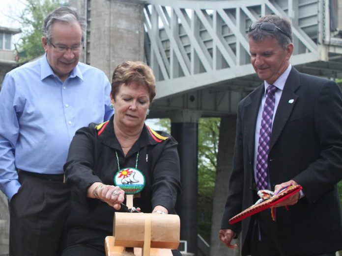 Chief Phyllis Williams of Curve Lake First Nation carving The Canadian Canoe Museum's symbolic paddle while Peterborough MPP Jeaf Leal and Peterborough County Joe Warden look on. The museum is engaging Indigenous peoples throughout the planning process. (Photo: The Canadian Canoe Museum)