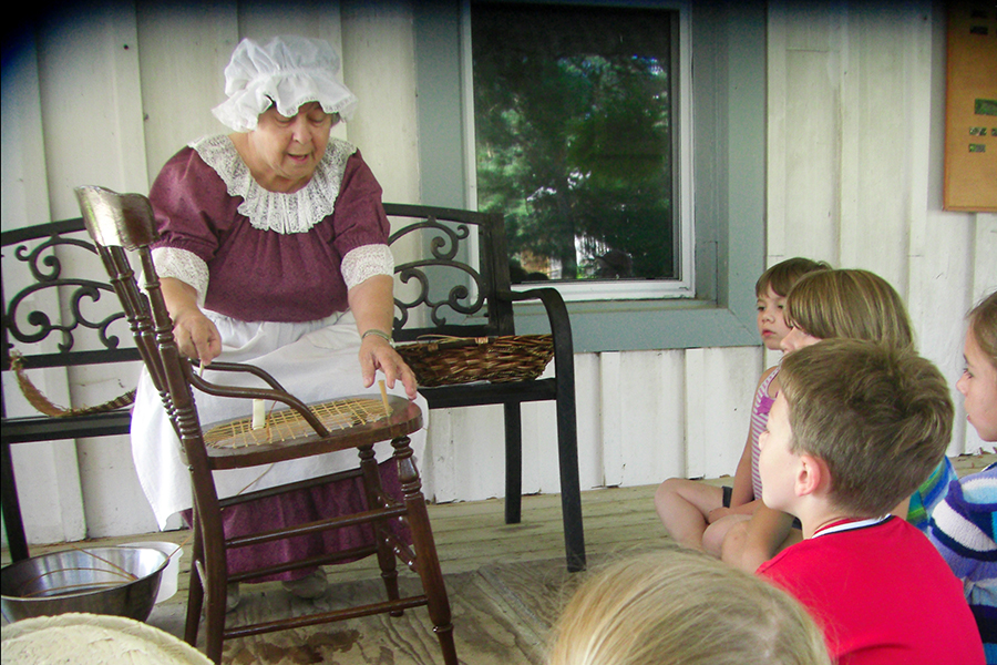 Children learn hands-on activities considered 'everyday' over a hundred years ago, like chair caning taught by volunteer Louise Plante. (Photo: Kawartha Settlers' Village)